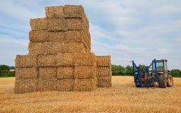 Staplat hö och en traktor royaltyfri fotografi