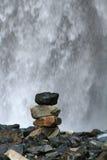 Staplat vaggar framme av vattenfallet Royaltyfria Foton