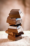 Staple Chocolate Tower. Tower composed of pieces of staple chocolate on a linen background for chocolate and cocoa concepts Stock Photography