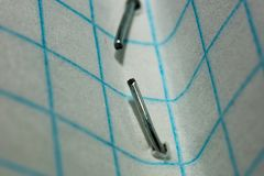 Staple fastener in a paper sheet in a cage macro. Staple fastener in a paper sheet in a cage close royalty free stock image