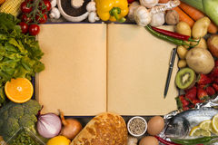 Staple Foods - Recipe Book - Space for Text. Staple foods - Fruit, Fish, Bread and Vegetables with the blank pages of a cookbook or recipe book - Space for text stock images