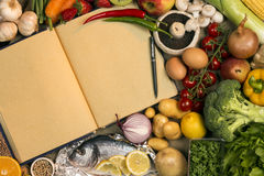 Staple Foods - Recipe Book - Space for Text. Staple foods - Fruit, Fish and Vegetables with the blank pages of a cookbook or recipe book - Space for text royalty free stock image