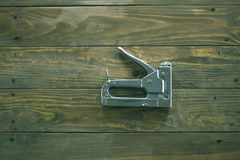 Staple gun on a wooden surface Royalty Free Stock Photography