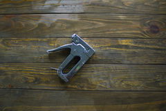 Staple gun on a wooden surface. Covered with impregnation Royalty Free Stock Image