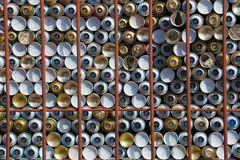 Staple of spray cans behind rusty bars Royalty Free Stock Photo