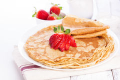 Staple of wheat golden yeast pancakes or crepes, with fresh strawberry on a wooden table. On a white background closeup Royalty Free Stock Photography