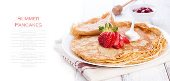 Staple of wheat golden yeast pancakes or crepes, traditional for Russian pancake week, with fresh strawberry on a wooden table. On a white background with place Stock Image