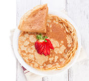 Staple of wheat golden yeast pancakes or crepes, traditional for Russian pancake week, with fresh strawberry on a wooden table. On a white background with place Royalty Free Stock Image