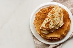 Staple of wheat golden yeast pancakes or crepes in a white plate closeup. Staple of wheat golden yeast pancakes or crepes in a white plate stock photo