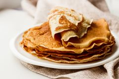 Staple of wheat golden yeast pancakes or crepes in a white plate closeup. Staple of wheat golden yeast pancakes or crepes in a white plate royalty free stock image