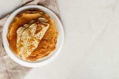 Staple of wheat golden yeast pancakes or crepes in a white plate closeup. Staple of wheat golden yeast pancakes or crepes in a white plate royalty free stock images