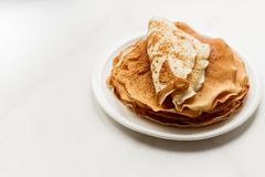 Staple of wheat golden yeast pancakes or crepes in a white plate closeup on a white background. Staple of wheat golden yeast pancakes or crepes in a white plate royalty free stock photography