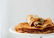 Staple of wheat golden yeast pancakes or crepes in a white plate closeup  on a white background. Staple of wheat golden yeast pancakes or crepes in a white plate royalty free stock images
