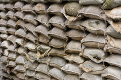 Stapled sandbags. Many bags filled with sand and stacked to a wall, fractional faultless and fractional broken-down and disrupted royalty free stock image