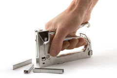 Stapler. Hand holding a stapler for repair of furniture Stock Image