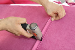 Stapler. Work as an industrial stapler on a covering of furniture a lather Stock Images