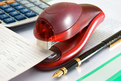 Stapler. Of red color, pen and calculator Stock Photography