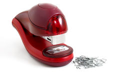 Stapler. Of red color are photographed near the paper-clips Royalty Free Stock Photography