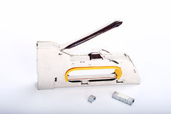 Stapler. Metal furniture stapler on plain background with staples next to it. This tool is used and marks from this are visible Royalty Free Stock Image