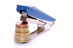 Stapler with coins. A stapler is holding a pile of coins ordered by size: the bigest down and the smallest up Stock Image