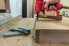 Red pneumatic stapler nails the bottom to the drawer royalty free stock photography