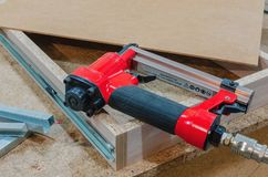Red pneumatic stapler nails the bottom to the drawer. Stapler gun protective gloves on wood board construction concept stock photo
