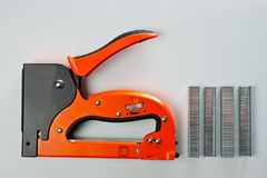 Stapler household, new, orange, reliable with staples royalty free stock photo