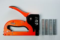 Stapler household, new, orange, reliable with staples royalty free stock image