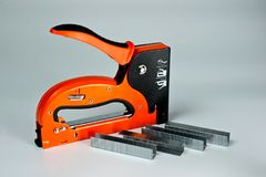 Stapler household, new, orange, reliable with staples royalty free stock photos