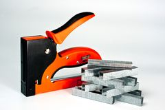 Stapler household, new, orange, reliable with staples stock photography