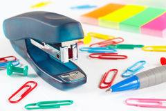 Stapler and multicolored stationery on white desktop close up Royalty Free Stock Photo