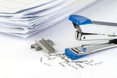 Stapler and pile of papers. Stapler with staples wires on white background royalty free stock images