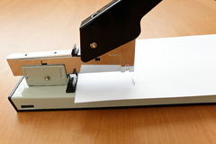 Stapler in progress, staple in the paper. On the table Stock Photography