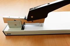 Stapler in progress, stapling paper. On the table Stock Photography