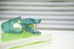 Stapler,staple remover on a green folder, Stock Images
