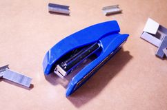 Stapler. Stapler blue. Stapler and staples. Stapler is on the table. Office. Office stapler. Stapler. Stapler blue. Stapler and staples. Stapler is on the table royalty free stock photography