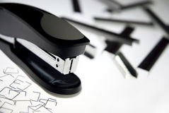 Stapler with staples. Black stapler with random staples around it royalty free stock photo