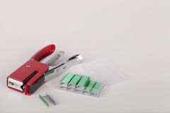 Stapler and staples. Miniature red stapler and green staples, isolated on a white background. Space for text stock images