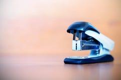Stapler on wooden table. One stapler on  wooden background Stock Photo