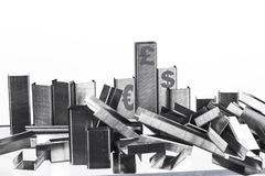 Piles of staples stacked to look like financial institutions. Staples arranged to be similar to bar charts or buildings falling like bad businesses Royalty Free Stock Images
