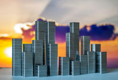 Staples arranged to form city skyline on a sunset background Royalty Free Stock Image