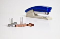 Staples e cucitrice meccanica che si trovano su una chiara superficie Fotografie Stock