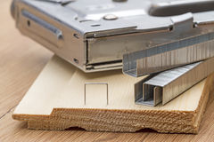 Staples for staple gun. Metal staples for staple gun on the board Royalty Free Stock Image