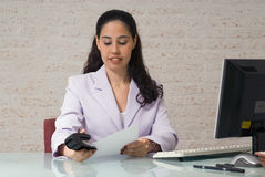 Stapling. A shot of young businesswoman stapling documents together Royalty Free Stock Photos