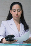 Stapling. A shot of a young businesswoman stapling, with the focus on the stapler Royalty Free Stock Photos
