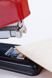 Stapling papers. Red stapler with multiple roles Royalty Free Stock Image