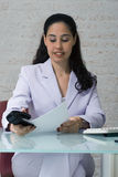 Stapling Papers. An isolated shot of a businesswoman stapling papers Royalty Free Stock Photography