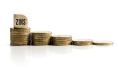 Staplungsmünzen, die abfallende Zinssätze mit dem Wort u. dem x22 symbolisieren; interest& x22; auf Deutsch Lizenzfreie Stockfotos