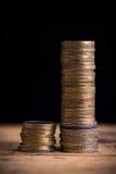 Staplungsmünzen, die Einkommensunterschied zwischen den reichen und normalen Einkommen zeigen Stockbild