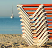 Staplungssonnenbetten auf einem sandigen Strand bei Sonnenaufgang Stockfoto